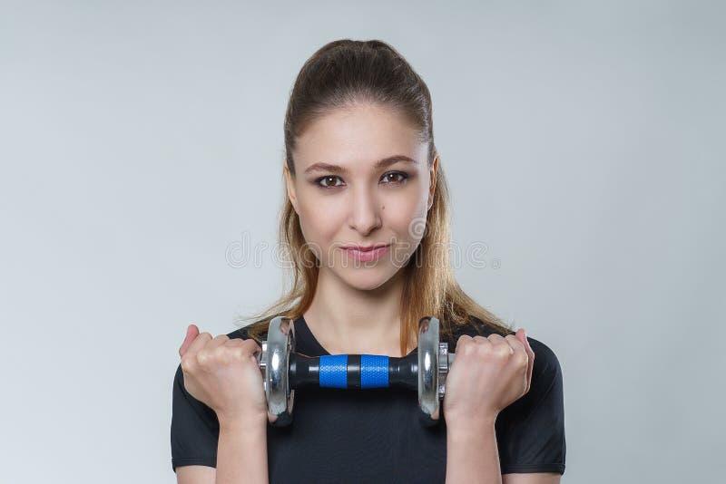 Mujer atractiva hermosa joven con el pelo moreno en una camiseta negra con pesas de gimnasia del metal, foto del deporte de la ap imágenes de archivo libres de regalías