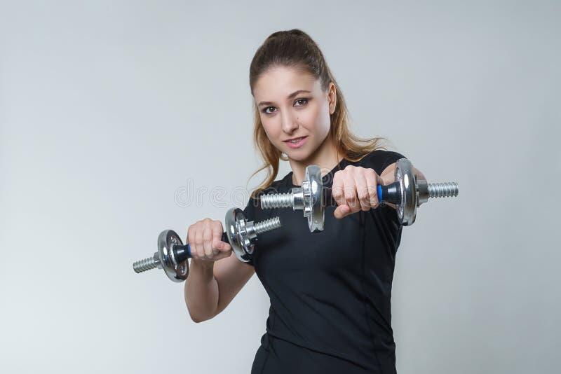 Mujer atractiva hermosa joven con el pelo moreno en una camiseta negra con pesas de gimnasia del metal, foto del deporte de la ap foto de archivo