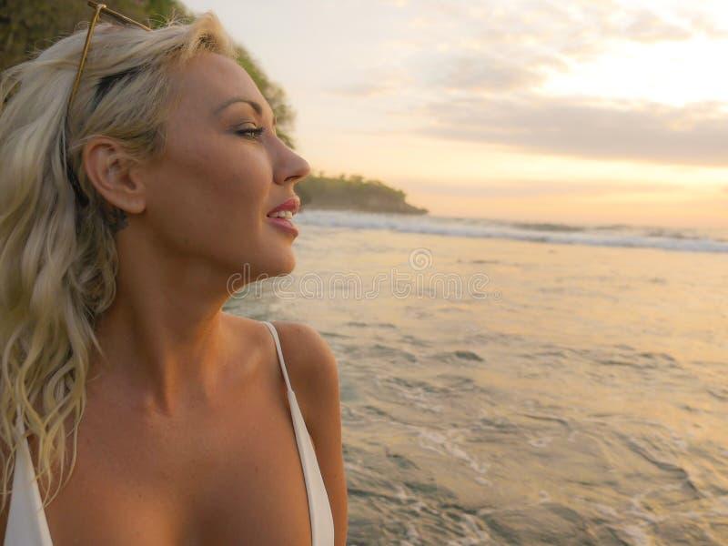 Mujer atractiva hermosa joven en el bikini que siente feliz y soñador relajado en la playa tropical hermosa del paraíso que disfr fotos de archivo