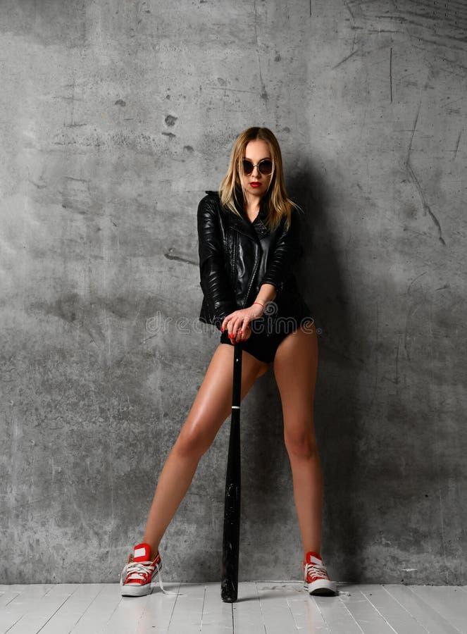 Mujer atractiva hermosa joven que presenta en chaqueta de la moda y bate de b?isbol negros del control de la ropa interior fotos de archivo libres de regalías