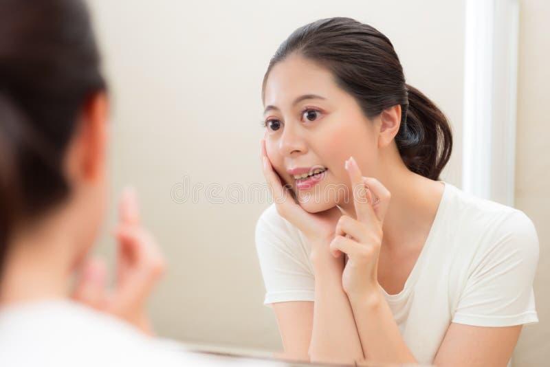 Mujer atractiva hermosa que comprueba la piel de la cara imagenes de archivo