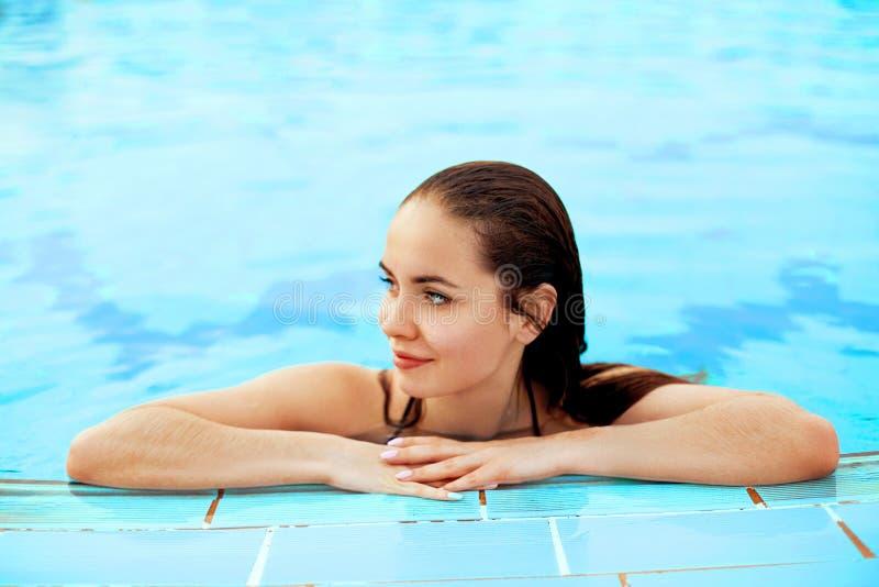 Mujer atractiva hermosa que se relaja en agua de la piscina Muchacha con la piel bronceada sana, cara magn?fica, imágenes de archivo libres de regalías