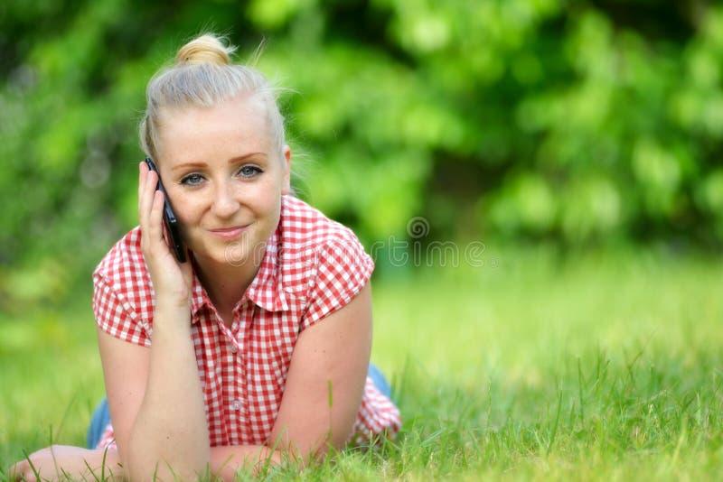 Mujer atractiva joven con el teléfono imágenes de archivo libres de regalías