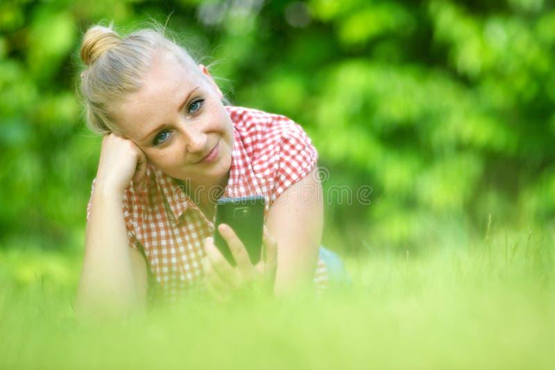 Mujer atractiva joven con el teléfono foto de archivo