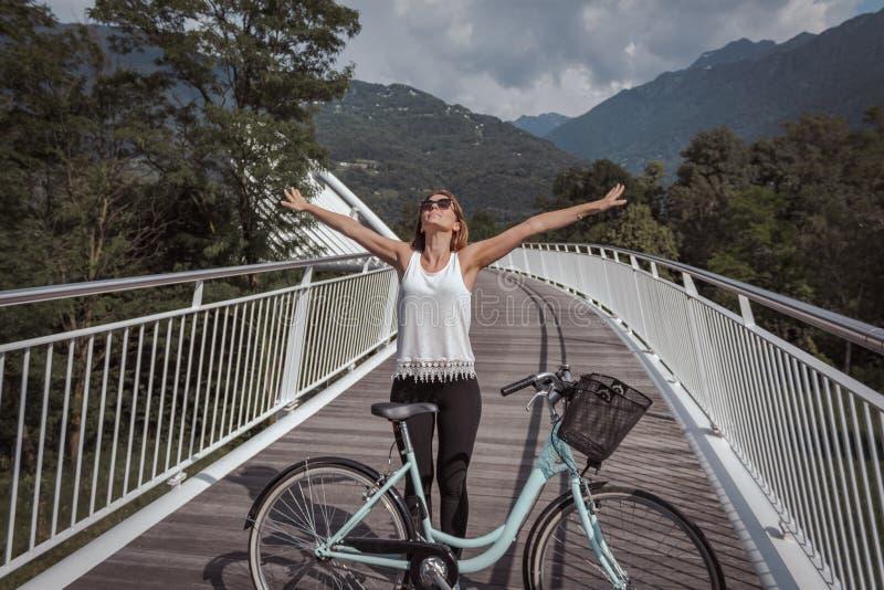 Mujer atractiva joven con la bicicleta en un puente imagen de archivo