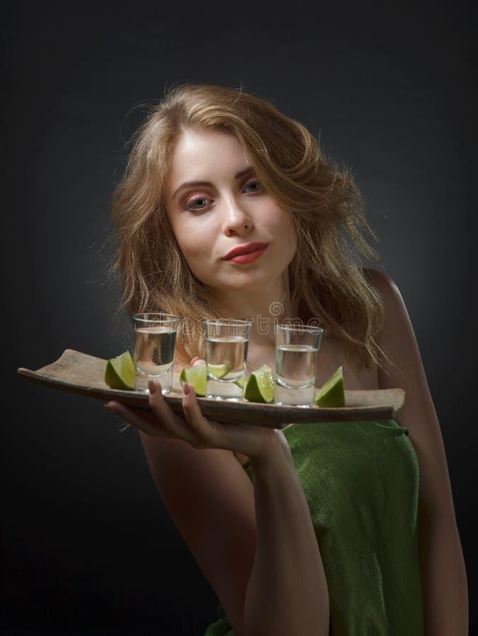 Mujer atractiva joven con las bebidas alcohólicas y las rebanadas de cal fotografía de archivo