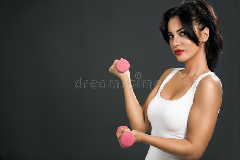 Mujer atractiva joven con pesas de gimnasia imágenes de archivo libres de regalías