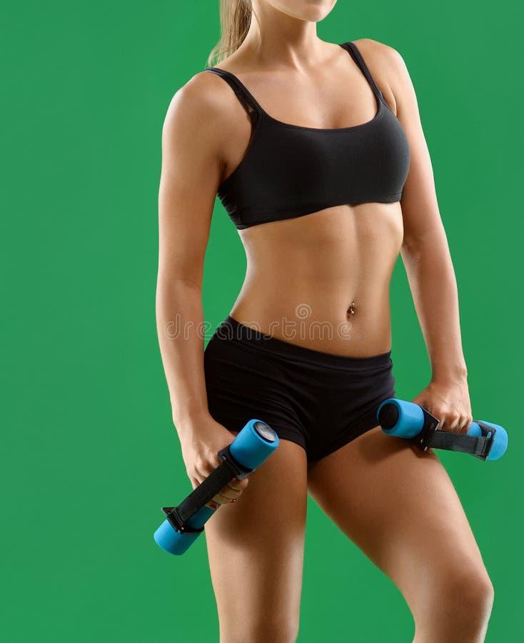 Mujer atractiva joven con pesas de gimnasia en sus manos que presentan en stu fotografía de archivo