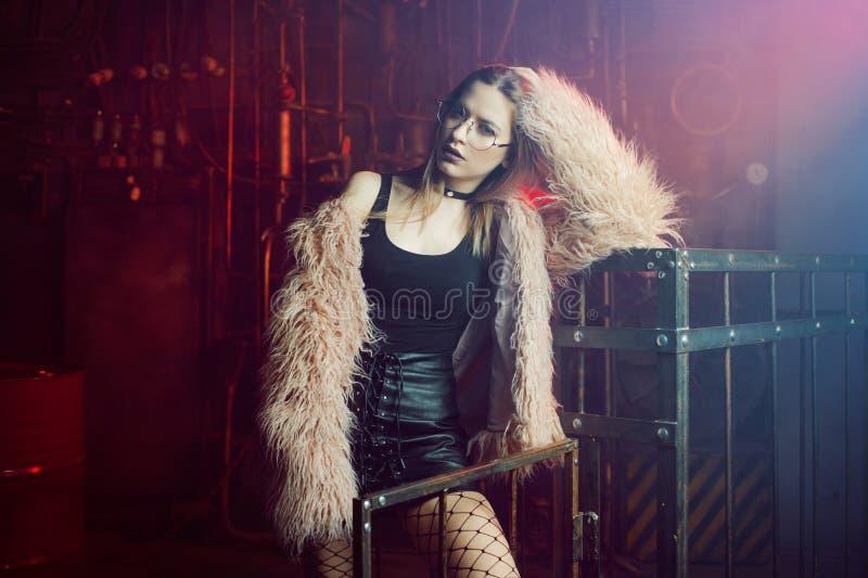 Mujer atractiva joven con ropa elegante Muchacha hermosa en el abrigo de pieles rosado mullido, fondo del Cyberpunk Luz de neón foto de archivo