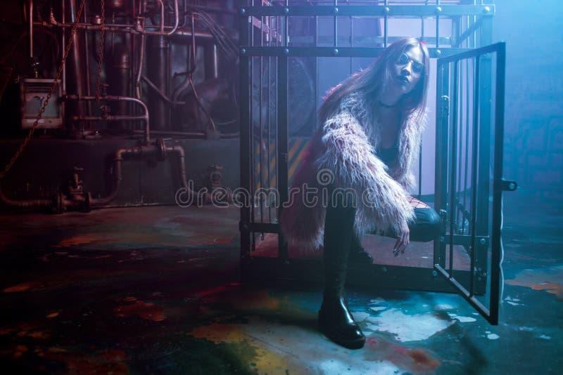 Mujer atractiva joven con ropa elegante Muchacha hermosa en el abrigo de pieles rosado mullido, fondo del Cyberpunk Luz de neón imágenes de archivo libres de regalías