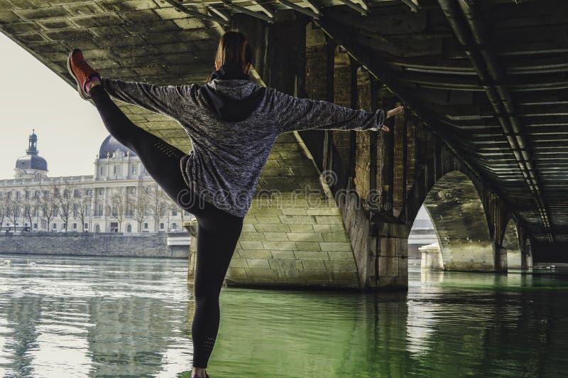 Mujer atractiva joven de la aptitud que hace ejercicio y que estira las piernas en la ciudad Arquitectura magnífica en el fondo imagen de archivo