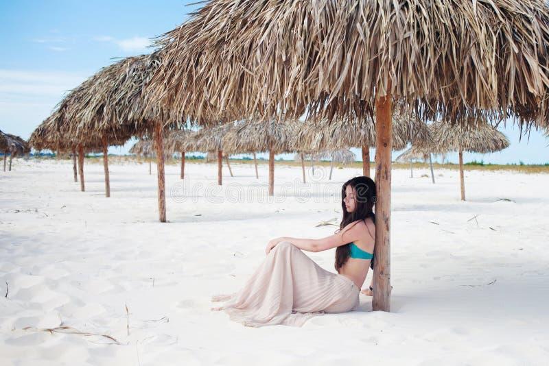 Mujer atractiva joven de vacaciones en el mar, sentándose en la arena debajo de un paraguas de la paja fotos de archivo