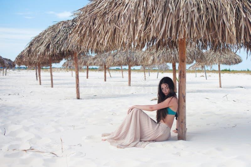 Mujer atractiva joven de vacaciones en el mar, sent?ndose en la arena debajo de un paraguas de la paja imágenes de archivo libres de regalías