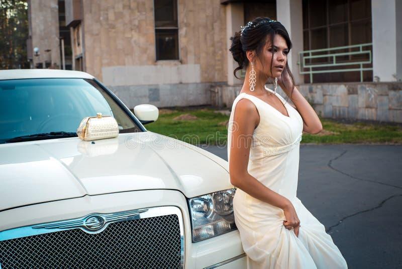 Mujer atractiva joven del VIP en el soporte del vestido cerca de la limusina blanca foto de archivo libre de regalías