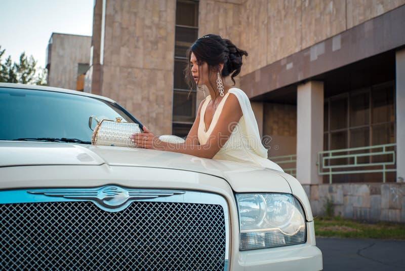 Mujer atractiva joven del VIP en el soporte del vestido cerca de la limusina blanca imagen de archivo
