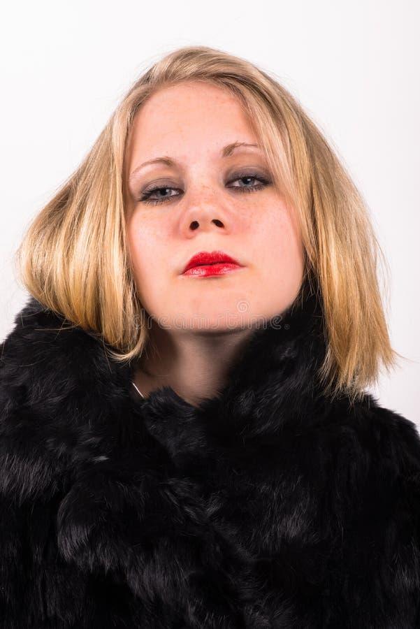 Mujer atractiva joven descarada en una piel negra imagen de archivo libre de regalías