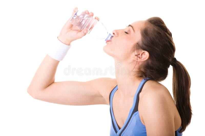 Mujer atractiva joven en agua de la bebida de la tapa de la aptitud foto de archivo libre de regalías