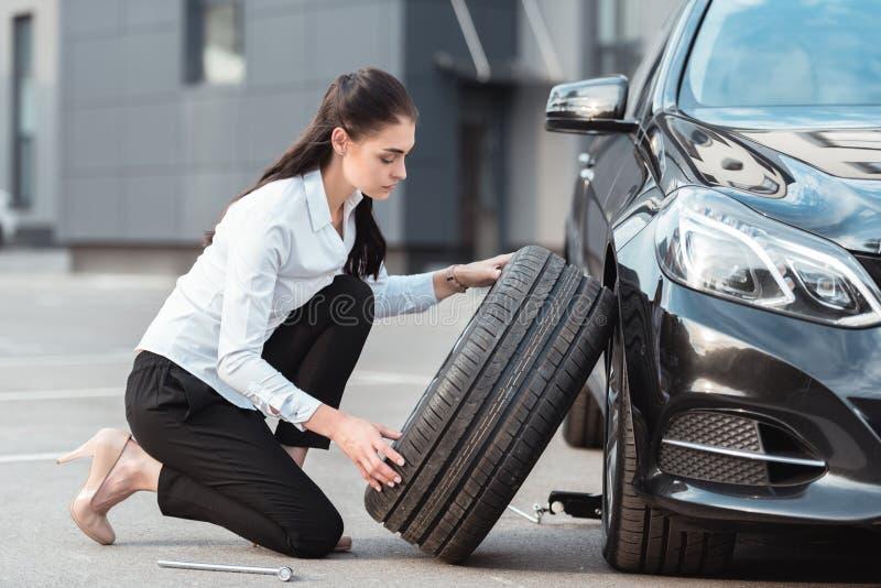 Mujer atractiva joven en el desgaste formal que sostiene un neumático de coche de repuesto fotos de archivo libres de regalías