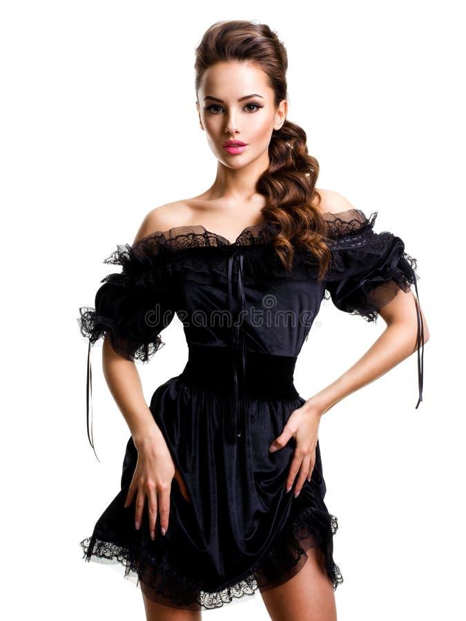 Mujer atractiva joven en el vestido negro que presenta en el estudio en el backgr blanco fotos de archivo libres de regalías
