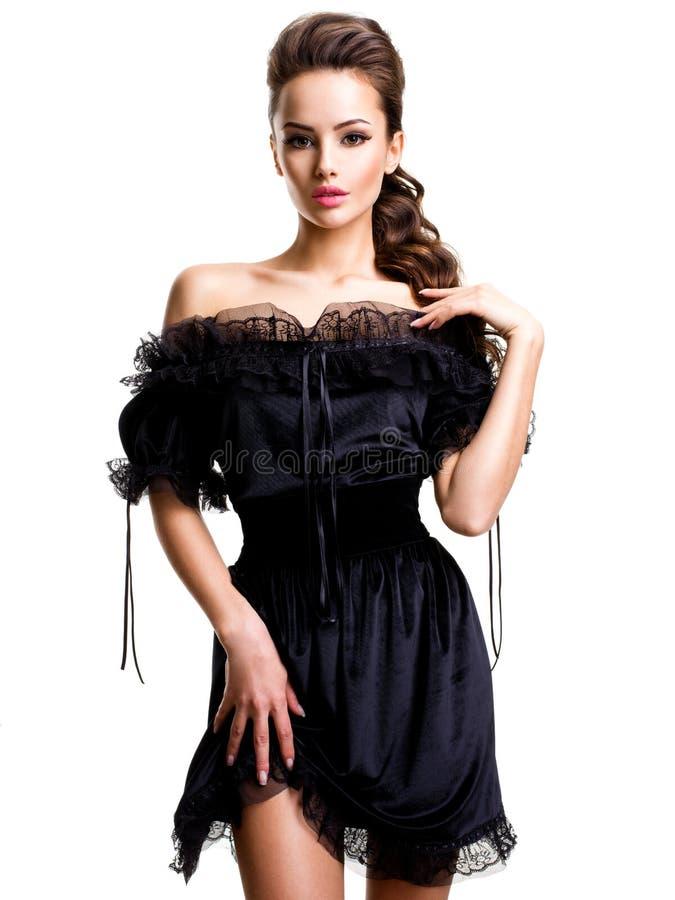 Mujer atractiva joven en el vestido negro que presenta en el estudio en el backgr blanco foto de archivo libre de regalías