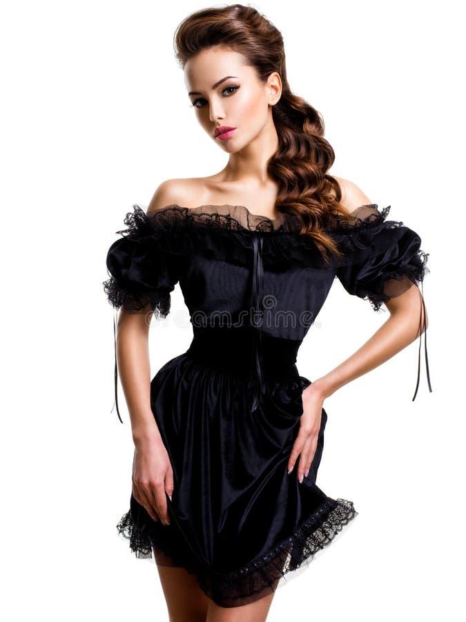 Mujer atractiva joven en el vestido negro que presenta en el estudio en el fondo blanco fotografía de archivo