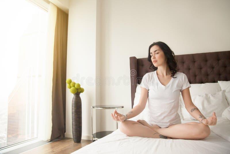 Mujer atractiva joven en la media actitud de Lotus en el dormitorio fotografía de archivo
