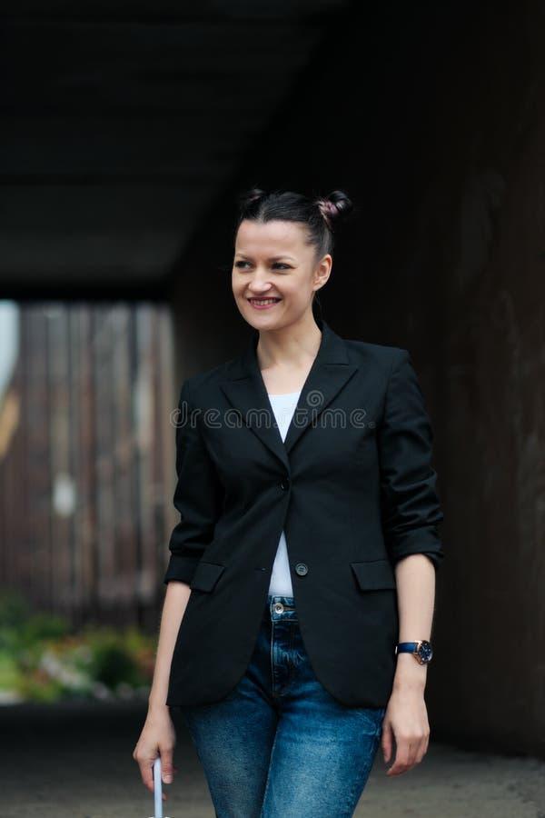Mujer atractiva joven en la presentación negra de la chaqueta y de los tejanos al aire libre contra el fondo del edificio fotografía de archivo