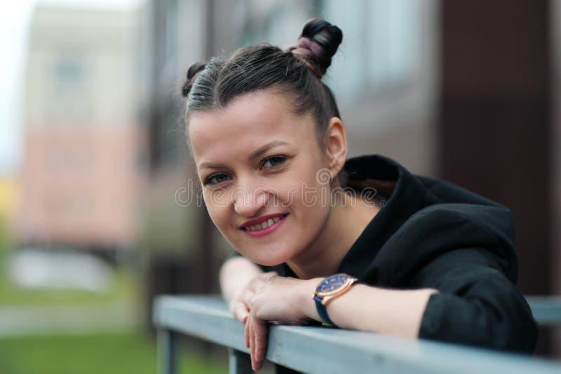 Mujer atractiva joven en la presentación negra de la chaqueta y de los tejanos al aire libre contra el fondo del edificio fotografía de archivo libre de regalías