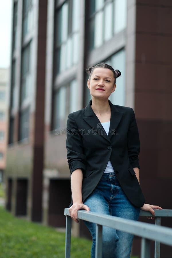 Mujer atractiva joven en la presentación negra de la chaqueta y de los tejanos al aire libre contra el fondo del edificio imagenes de archivo