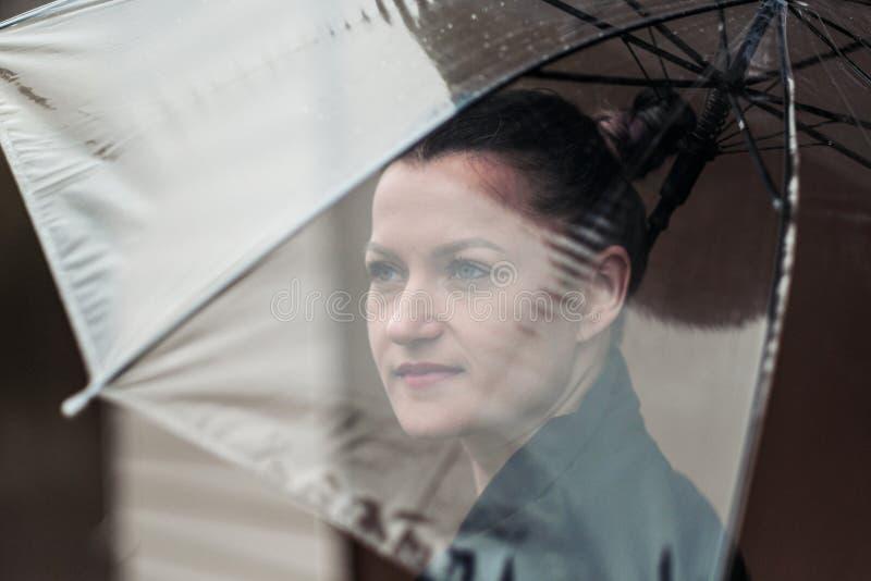 Mujer atractiva joven en la presentación negra de la chaqueta y de los tejanos al aire libre contra el fondo del edificio foto de archivo libre de regalías