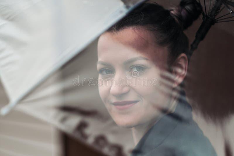 Mujer atractiva joven en la presentación negra de la chaqueta y de los tejanos al aire libre contra el fondo del edificio imagen de archivo