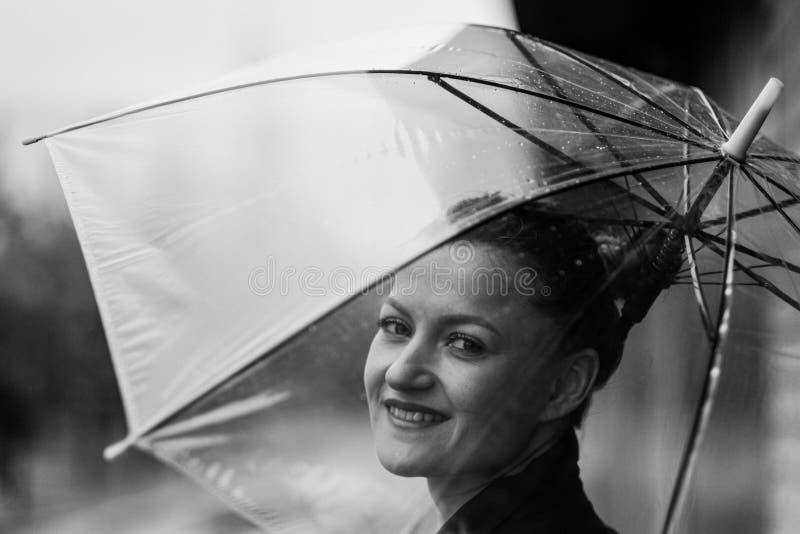 Mujer atractiva joven en la presentación negra de la chaqueta y de los tejanos al aire libre contra el fondo del edificio fotos de archivo