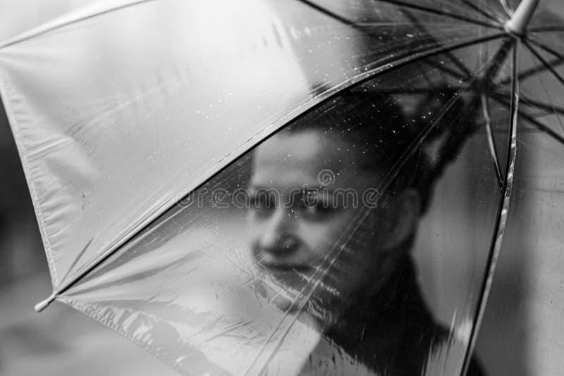 Mujer atractiva joven en la presentación negra de la chaqueta y de los tejanos al aire libre contra el fondo del edificio imagen de archivo libre de regalías