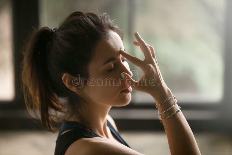 Mujer atractiva joven en la ventana de la nariz alterna que respira, vagos del estudio foto de archivo libre de regalías