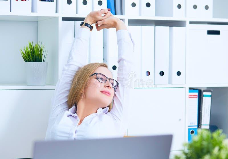 Mujer atractiva, joven en los vidrios que estiran en su lugar de trabajo y que sonríen en la oficina imagenes de archivo