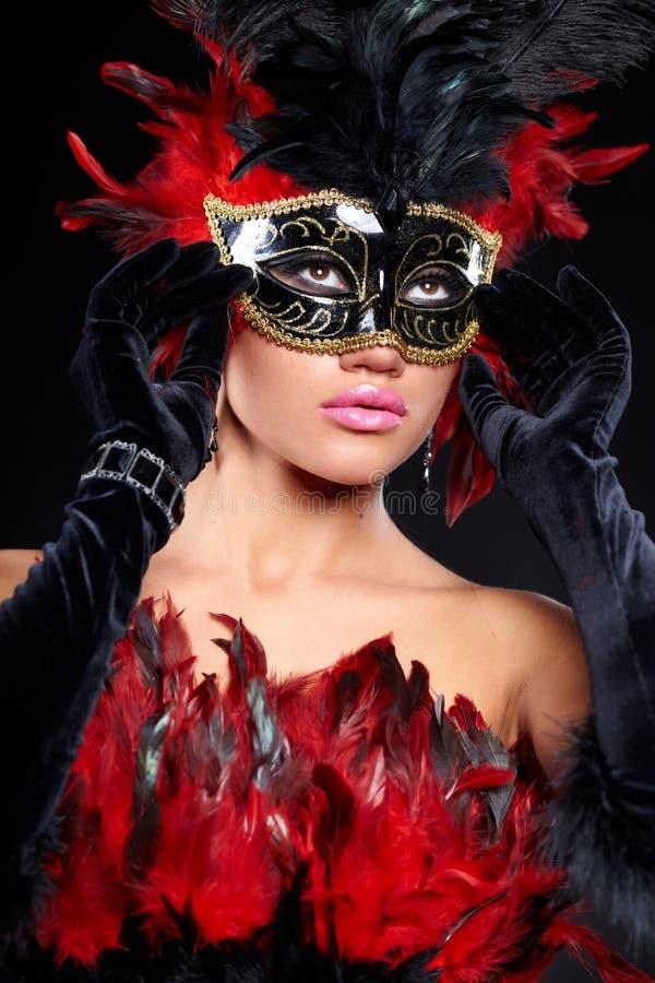 Mujer atractiva joven en media máscara del partido negro foto de archivo