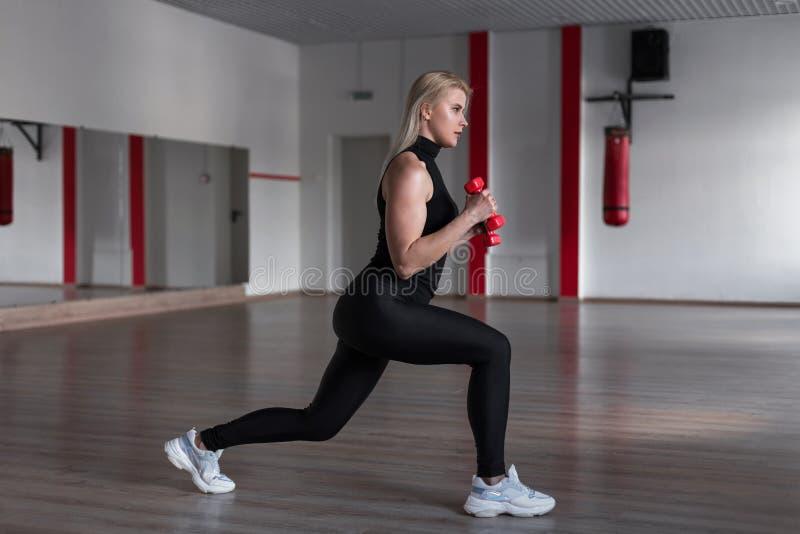 Mujer atractiva joven en polainas negras en la camiseta de los deportes que hace ejercicios con pesas de gimnasia en manos en el  imagen de archivo