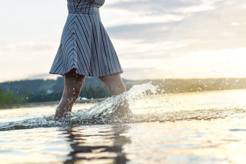 Mujer atractiva joven en puesta del sol Agua que salpica al caminar fotos de archivo