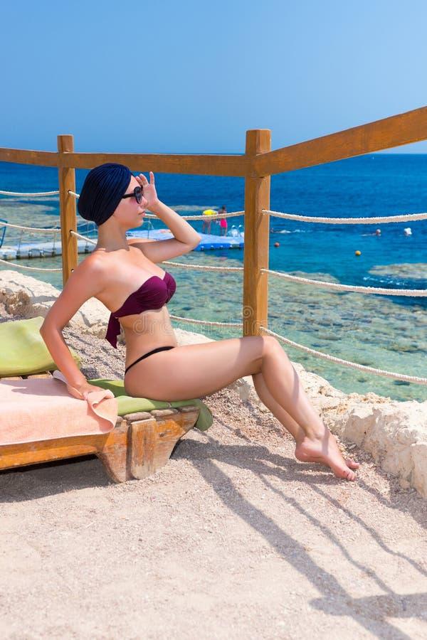 Mujer atractiva joven en turbante femenino y las gafas de sol que sientan o imágenes de archivo libres de regalías