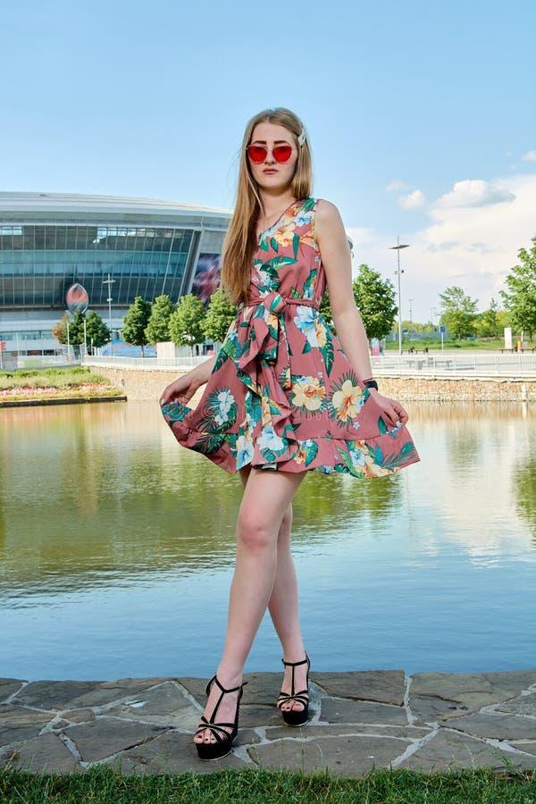 Mujer atractiva joven Gafas de sol rojas, vestido del color Retrato del ` s de la muchacha Fondo del estadio de f?tbol imágenes de archivo libres de regalías
