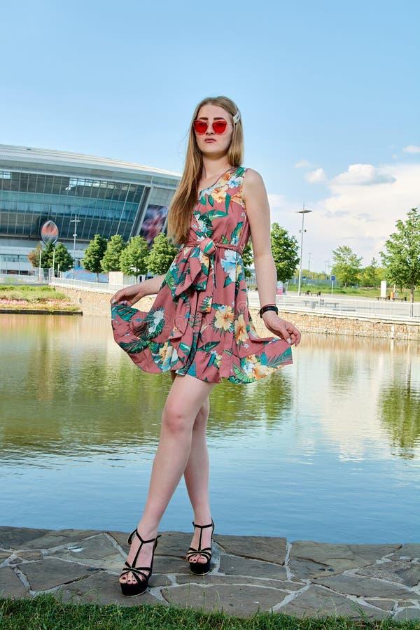 Mujer atractiva joven Gafas de sol rojas, vestido del color Retrato del ` s de la muchacha Fondo del estadio de f?tbol fotografía de archivo libre de regalías