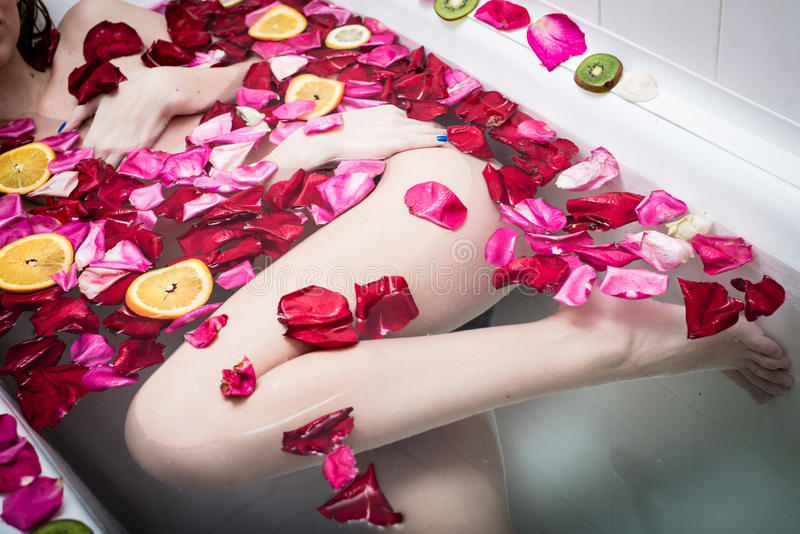 Mujer atractiva joven hermosa que se relaja en bañera del balneario con los pétalos color de rosa de la flor y las rebanadas de f foto de archivo