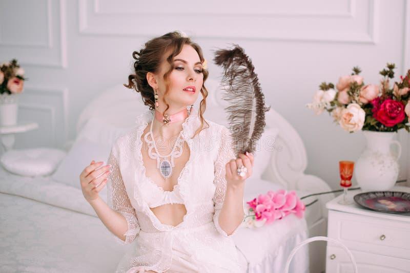 Mujer atractiva joven hermosa que se sienta en la cama blanca, vestido blanco del cordón que lleva, pelo adornado con las flores  imagenes de archivo