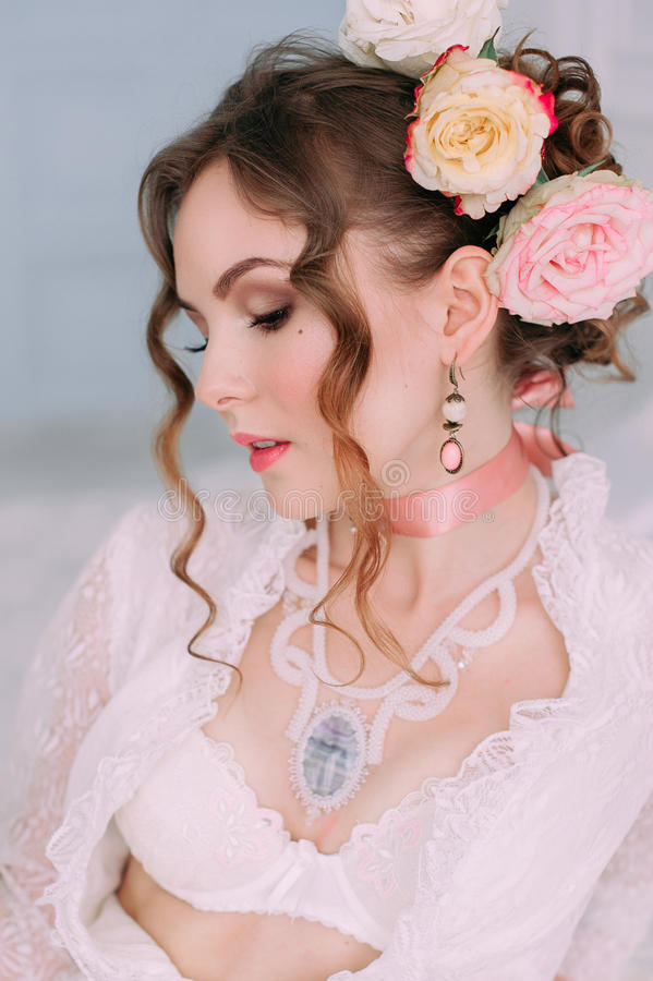 Mujer atractiva joven hermosa que se sienta en la cama blanca, vestido blanco del cordón que lleva, pelo adornado con las flores  fotos de archivo