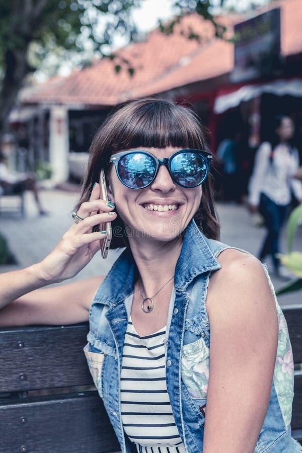 Mujer atractiva joven hermosa que usa el smartphone que se sienta en un banco en el parque Isla de Bali, Indonesia imagenes de archivo