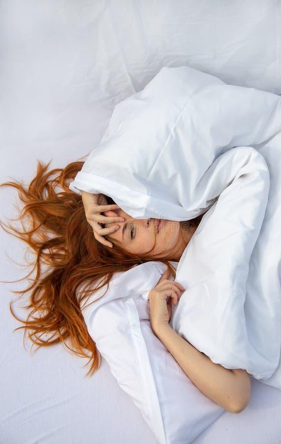 Mujer atractiva, joven, pelirroja, pelo salvaje en las hojas, cara media debajo de la almohada que miente en hojas blancas suaves foto de archivo libre de regalías