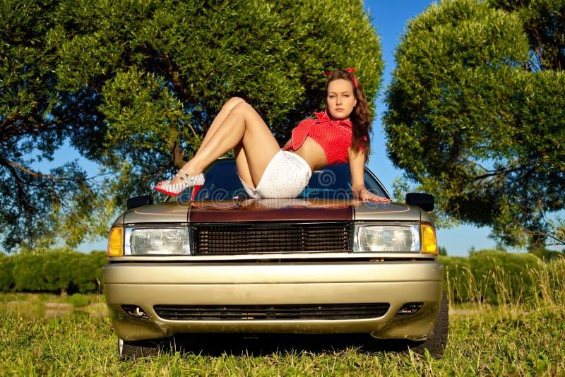 Mujer atractiva joven puesta en capo del coche imagenes de archivo