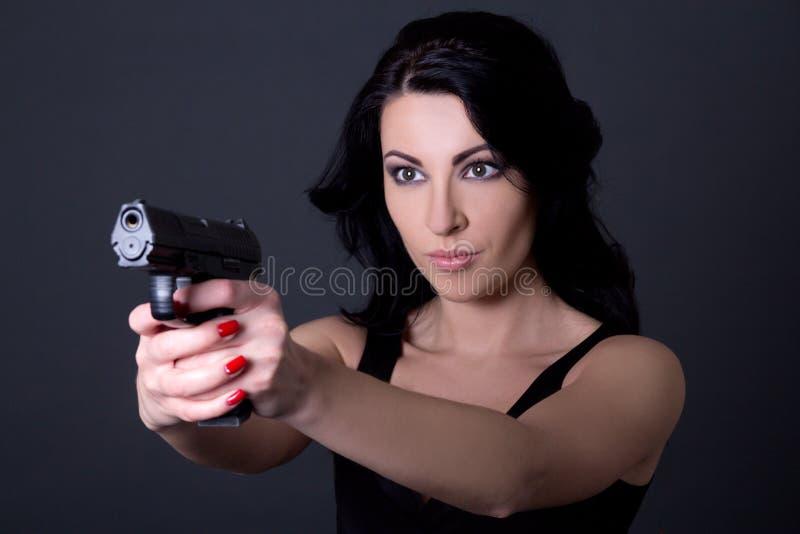 Mujer atractiva joven que apunta con el arma sobre gris fotografía de archivo