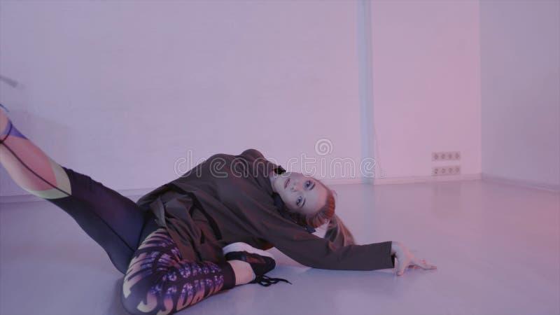 Mujer atractiva joven que baila danza moderna en pasillo de danza acci?n La mujer joven por completo de la energía y de la sexual fotos de archivo libres de regalías