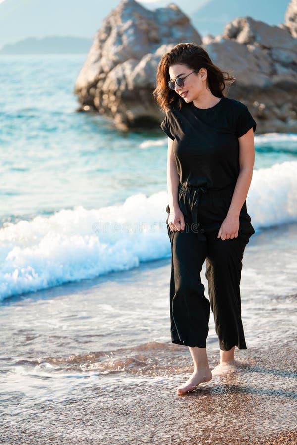 Mujer atractiva joven que camina en una playa soleada en la orilla Viajero y blogger foto de archivo libre de regalías